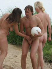 Swingers getting naked at the nude beach and laughing, playing and touching each other.