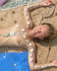 Nude cutie on the beach decorates herself with pebbles